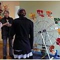 藝術家(面向鏡頭者)正向訪客解釋她的創作