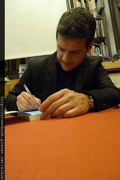 一臉認真的Musso,三天下來簽了數百本書,小編好想幫他抓龍喔.JPG