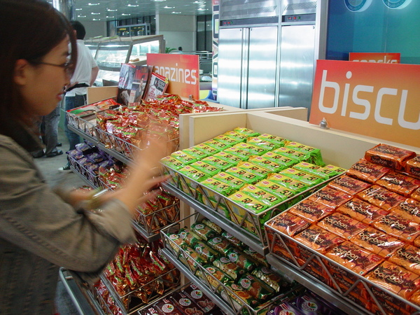 小do在研究機場內的雜貨零食。