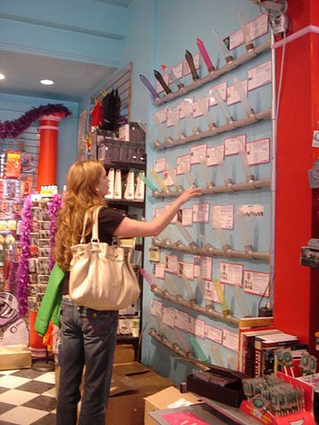 金髮美女仔細研究整面牆的保險套