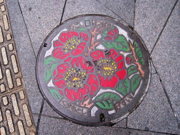 平整又可愛的人孔蓋,上面應是熊本市花「肥後山茶花」