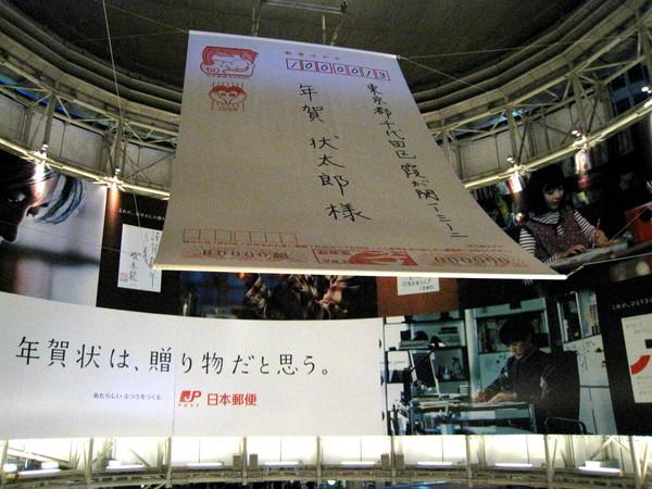 六本木車站電扶梯上空,懸掛一張大型賀年片,是郵局鼓勵民眾多寄賀年片的廣告