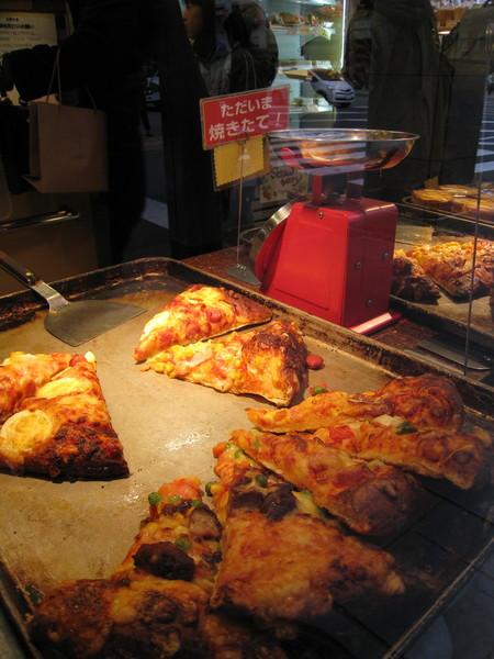 又在熊本街頭的麵包店,外帶一片現烤比薩,我們是豬