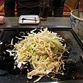 老闆的專業料理示範。步驟一:將碗中的料倒在鐵板上,麵糊湯汁暫留碗內