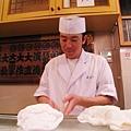 師傅一邊捏壽司,邊跟一位馬來西亞女顧客學馬來文的問候語