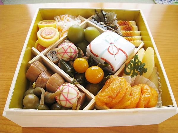 第二層:左上是紅白錦系卷、醋漬紅白蘿蔔絲;左下是干貝煮、瓢箪粕漬、手毬麩;右上是小魚甘露煮、松笠焼目射込真丈;右下是魚卵、蜜漬杏桃、壽字昆布