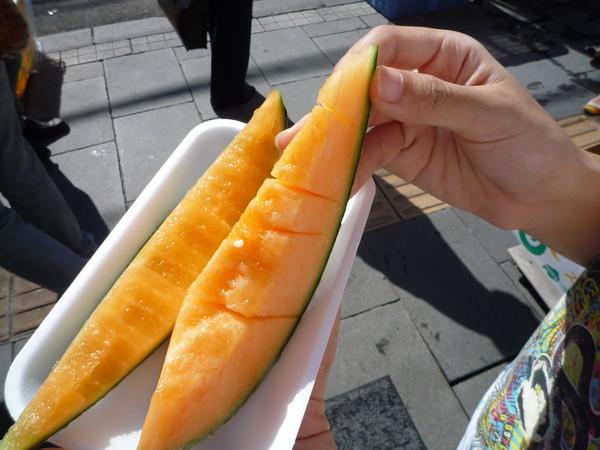 超甜的哈密瓜一切一百日圓,老闆幫我們分成兩片,當街站著吃