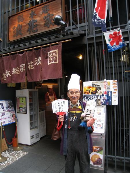 浪花家的老闆週末常會在店門口,拿著他的Q版娃娃陪遊客合照