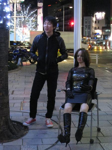 他可能是行動藝術家?站在假人旁怡然自得,似乎想觀察路人的反應
