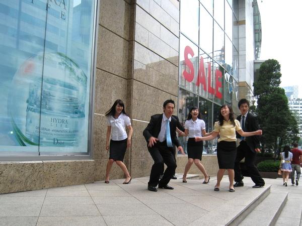 在樂天百貨門口當街擺跳躍pose給同事拍照