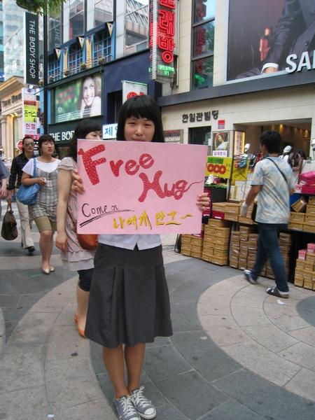 明洞鬧區好多高舉「Free Hug」海報的制服女學生,大白很不要臉的真的上前去要了一個免費擁抱