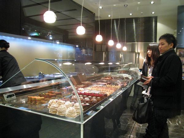 正在等店員包裝甜點的情侶顧客看起來好開心