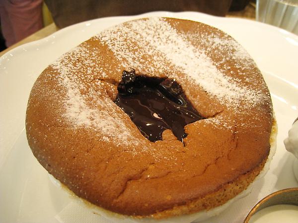 在舒芙蕾上挖一個洞,淋進巧克力醬和鮮奶油食用