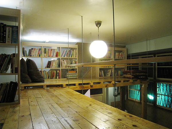 木板夾層是一個空中小書房,書架上有不少藏書和舒服的靠墊