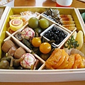 第二層中央菜色:右邊瓷盒內是甜黑豆、下方是金蜜柑煮、上方是梅甘露煮、左方底部是穴子八幡卷、彩線小球是手毬麩