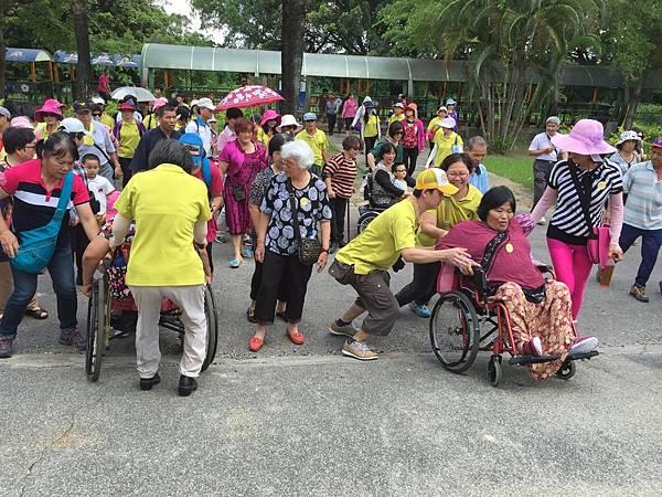 義工伙伴協助身障朋友上坡.JPG