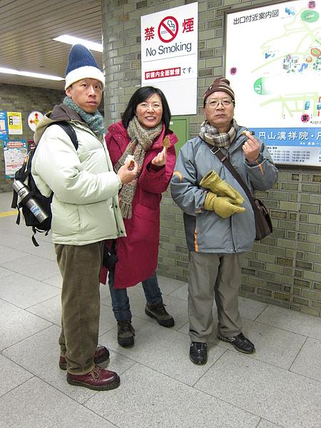 在地鐵路邊吃麵包的三人