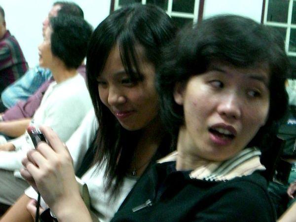 在聽講時玩相機的兩人