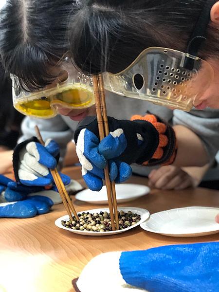 大葉大學休閒系學生戴手套用筷子夾豆子,體驗長輩的不便.png