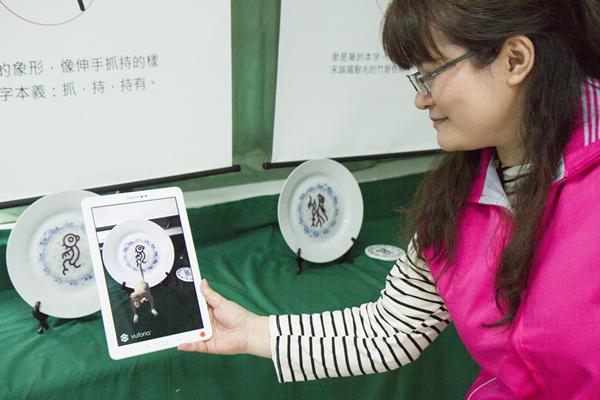 彰安國中輔導主任陳詩靖手持平板感應現場的甲骨文雕塑或圖案.png