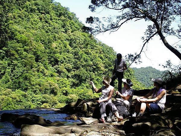 在瀑布上方休息的旅人