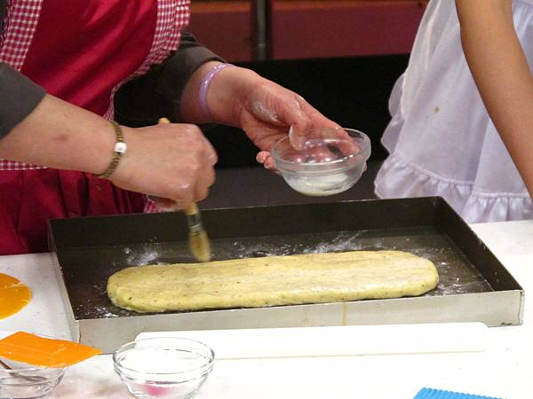 將鬆弛好的麵糰擀開成厚度約0.5-0.8公分左右,表面刷上牛奶灑上百里香