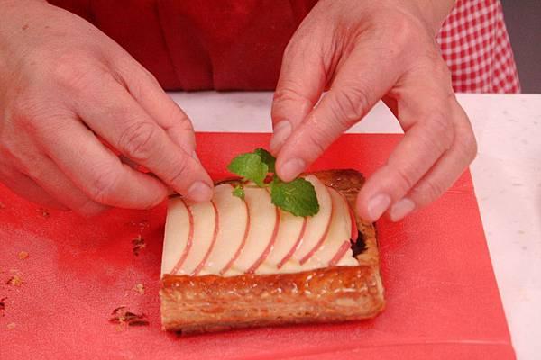 青森蘋果派 做法:將放涼的杏仁餡派皮上擠上卡士達醬,再鋪上切片的蘋果片,刷上透明果膠放上薄荷葉裝飾即可