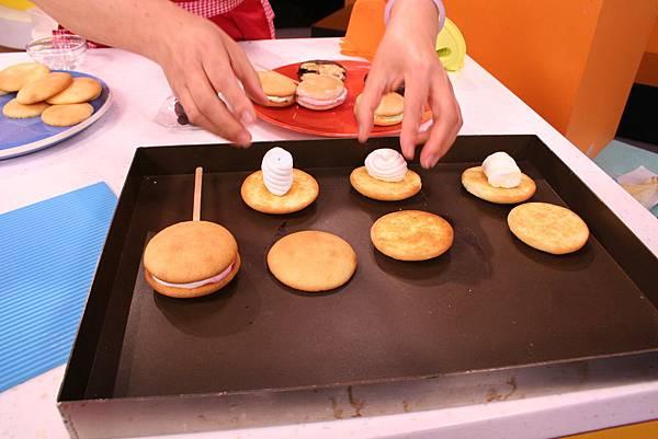 將烤好的蛋糕體配對後,取半數的蛋糕體放上棉花糖後放入烤箱中烤至棉花糖變軟,再放上木棒及一片蛋糕體壓緊成夾心狀