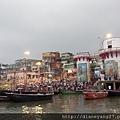 """坐在木船上、從河上拍攝恆河岸上的晨景。粉紅色的雙柱建物是知名的Rajendraprasad ghat,以Dr. Rajendra--印度第一任總統為名,在印度1950年正式變成一個共和國時Rajendra就任為首任總統。此處最早期其實是Dashashvamedha Ghat的一部分;西元3世紀時還曾是賣馬匹的交易地點、被稱為""""Ghoda"""" (horse) ghat。"""