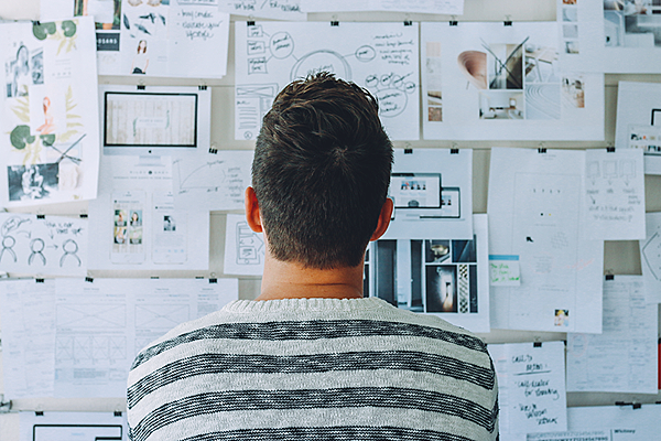 Canva - Man Wearing Black and White Stripe Shirt Looking at White Printer Papers on the Wall.png