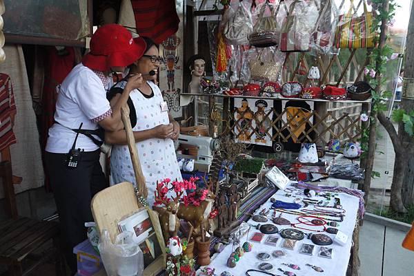 霧社街裡也有原住民風情攤販進駐,攤販老闆正在為大家介紹他的手作商品。.JPG