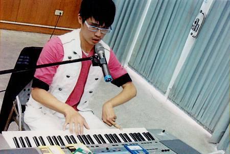 圖2-陳贈友用僅能動的六根指頭彈奏琴鍵。