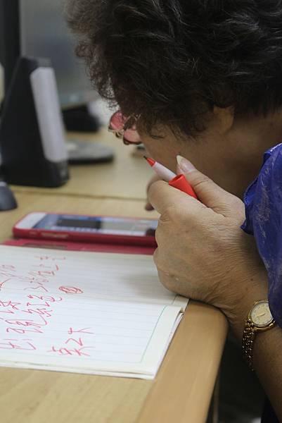 斗大的字跡,梅姐勤作筆記,練習操作視障語音手機。