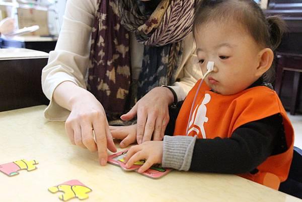 p14-15主圖:職能治療師顏維貞藉由拼圖,教小艾認知、訓練精細動作。.JPG