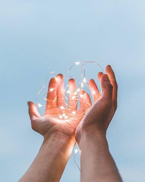 封面-一雙手捧著美麗的燈火,像很多隻螢火蟲在手裡飛舞。