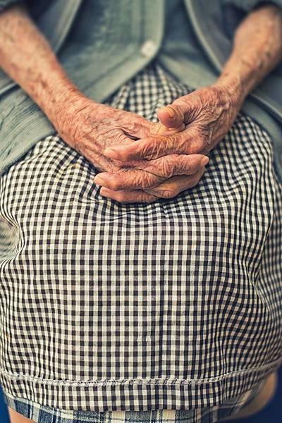 情境圖-皺皺的手,交叉,放在格子裙上,好似在等待。