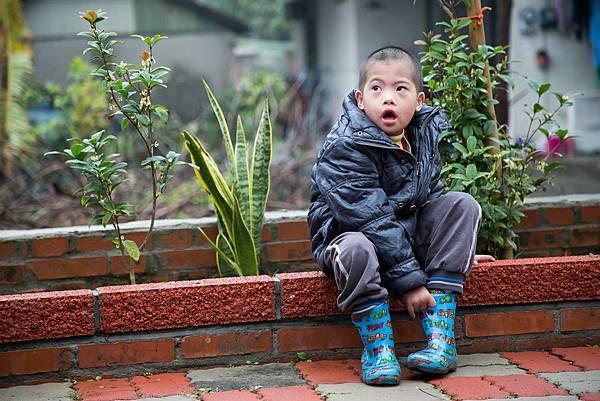 圖說:走到戶外的安安在學習穿雨鞋。