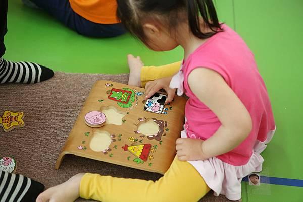 圖說:課堂上,孩子選擇感興趣的教具來操作,試著自己玩拼圖遊戲,家長在一旁觀察。