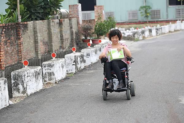 圖說:林文君坐著電動輪椅,外出寄送包裹訂單。