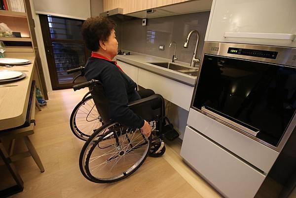 (圖說:長輩部分失能不代表完全喪失能力,降低流理台高度、櫃體內縮設計,感應式燈具與水龍頭設計,讓輪椅長輩可以收放腳,重拾下廚的樂趣。)