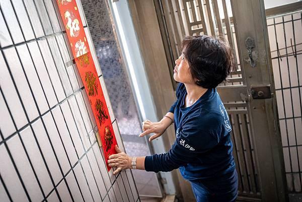 (圖說:居服員陳來珠幫阿嬤在門口貼上春聯,迎接準備來臨的農曆年。)
