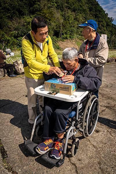 (圖說:用餐時,李木根細心協助住民們喝水、開點心袋子。)