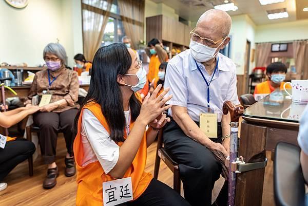 圖說:同學蹲下來,與坐著的爺爺聊天。