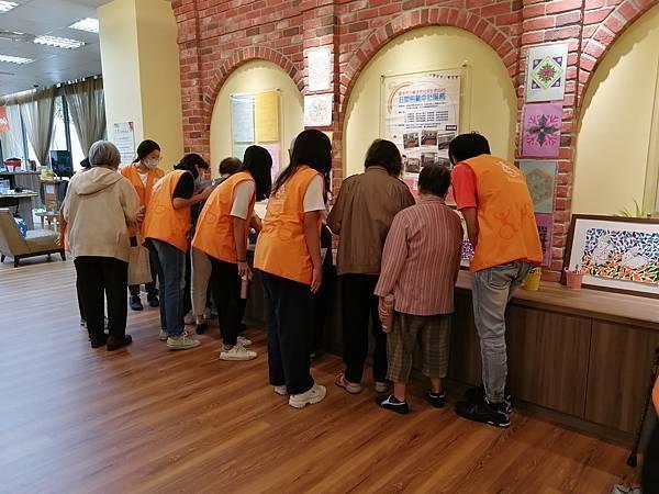 圖說:奶奶與志工聚在矮櫃前,欣賞美勞作品。