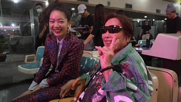 高齡95歲的玉蘭阿嬤(圖右)在片場與工作人員開心合影留念