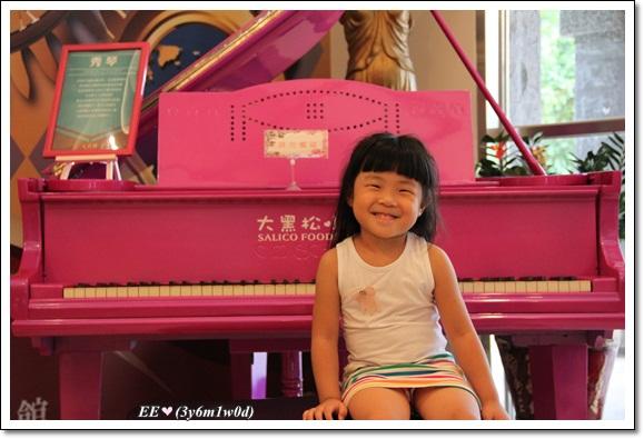 EE坐在粉紅鋼琴前