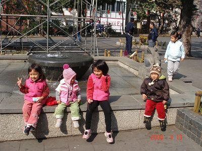 小孩排排坐噴水池邊