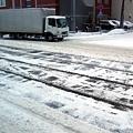 電車軌道和車道上的雪被壓得髒髒的