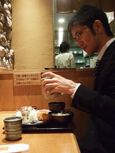 斯文的上班族自己來吃,神情認真地替高麗菜絲淋上醬汁
