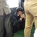 中年男子蹲在電車裡玩手機